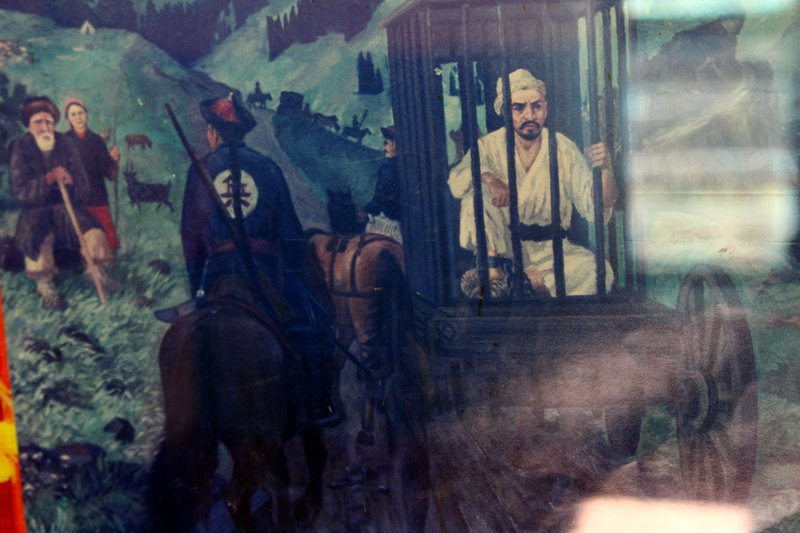 Painting of man in a cage being carried on the back of a horse-drawn cart