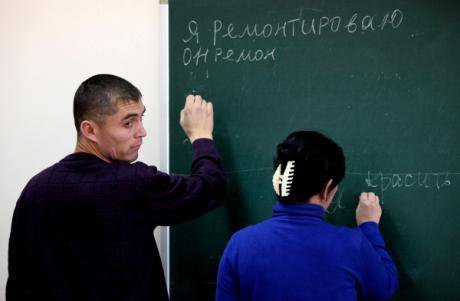 A Russian lesson in Vladivostok. Students attempt to conjugate the verbs 'to repair' and 'to paint'.