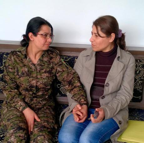 Two women sit holding hands, one of them in combat fatigues.