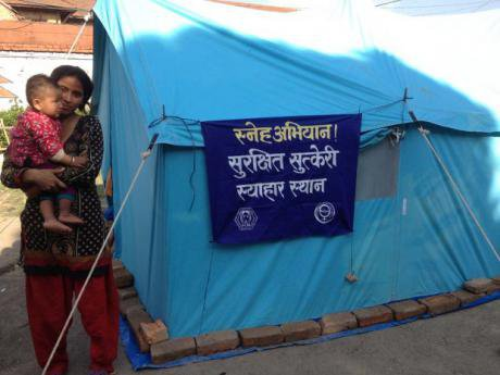Woman holds child beside an aid tent