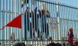 Three people climbing a high, razor-wire-topped fence. Red flag in the foreground.