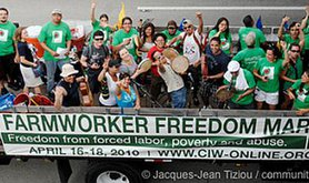 Crowd of people wearing green t-shirts behind a large banner reading 'Farmworker freedom march'