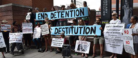 Group of people holding banners and posters, which call for the of end destitution and detention.