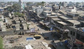 Photo of waste ground and shanty-like buildings in a cityscape