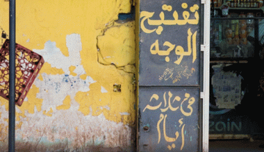 A wall with a painted sign in Arabic