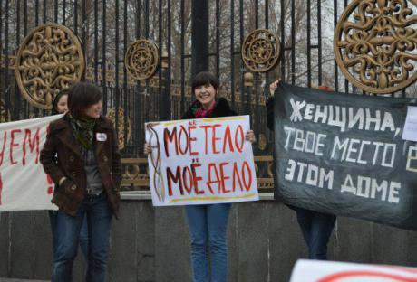 Women holding banners outside a large gate