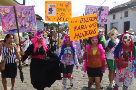 Women march through a street holding colourful placards