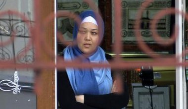 A hijabi woman stares out of a shop window.