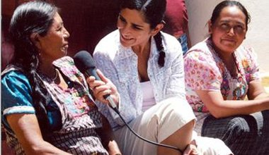 Woman with microphone sits on steps between two women in bright sunlight
