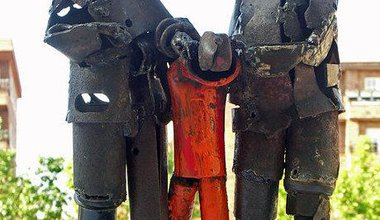 Protest sculpture in metal against Guantanamo, with stylised camp guards and helpless detainee