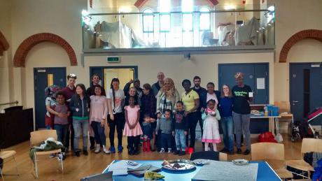Smiling men, women and small children stand in centre of a church hall.