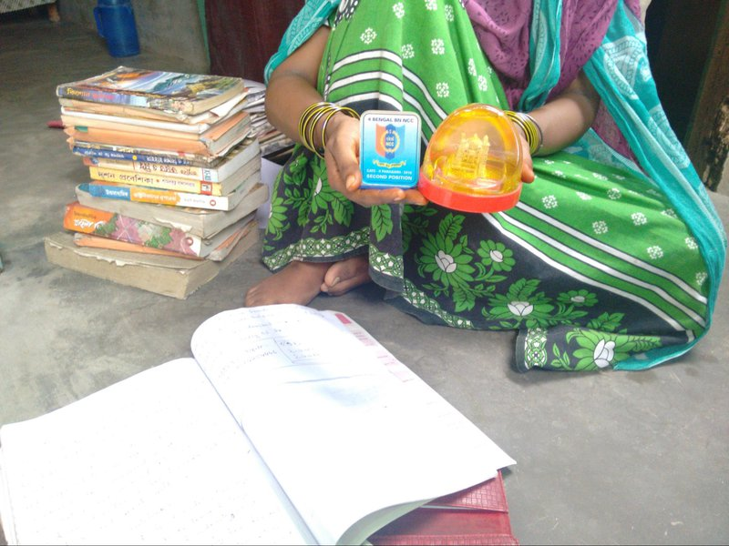 A survivor's mother in West Bengal, with items belonging to her daughter who was gang-raped and murdered.
