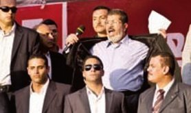 President Morsi surrounded by body guards, opening his jacket to show his shirt.