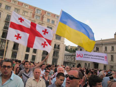 Georgian & Ukrainian flags fly alongside a banner opposing any compromise with 'collaborators'