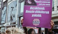 Woman holding a placard with an image of a young woman alongside Turkish text
