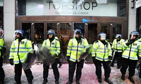 Police guard a paint spattered Top Shop during anti-cuts protest