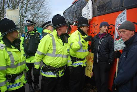 Police film and speak to a man with a placard stood against a big red bus