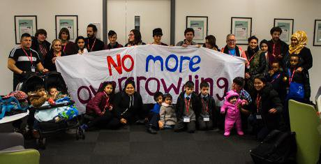 People of all ages including babies huddled together. They hold a large banner: no more overcrowding.
