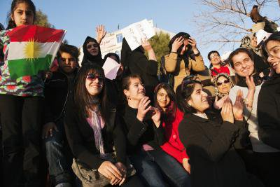 Crowd of women with flag smiling and clapping