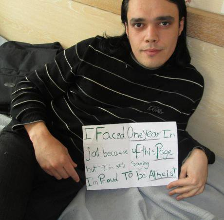 Man holding sign saying 'I faced one year in jail because of this page, but I'm still saying I'm proud to be Atheist'