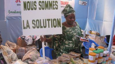 Woman at a market stall holding a placard saying 'Nous sommes la solution'