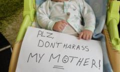 Baby holding a sign reading 'please don't harras my mother'