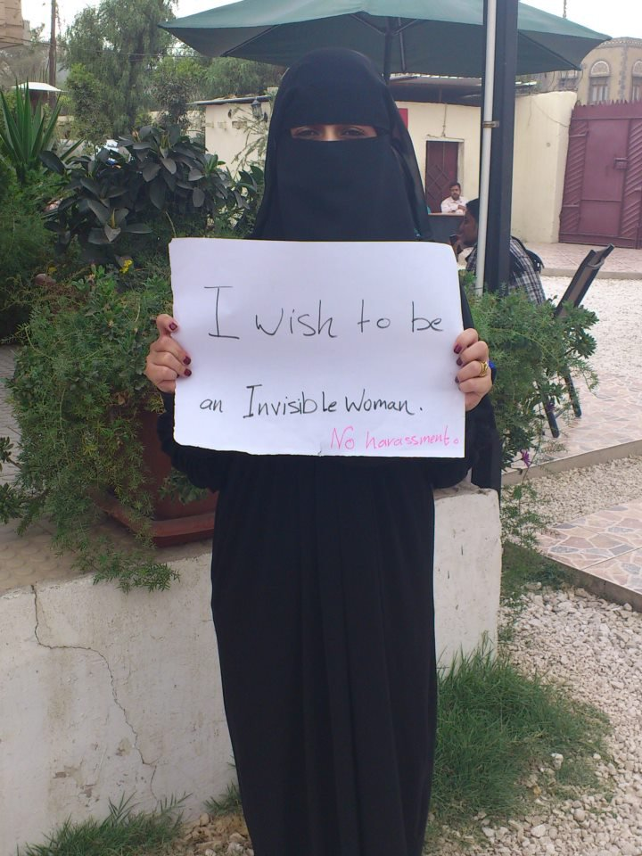 Woman in full niqab with sign reading: I want to be an invisible woman